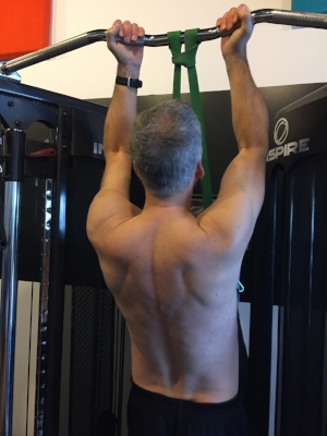 To teach Gordon what good scapular retraction looks like in a chin-up, his coach had him perform a few reps shirtless so that he could see the difference.