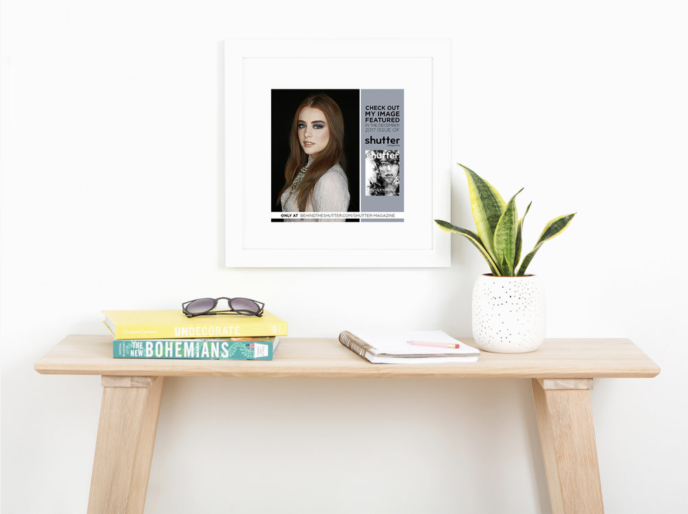table with books and sunglasses & framed picture of a girl hanging on the wall