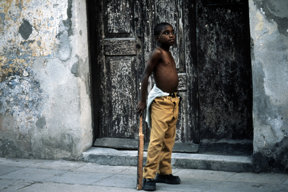 Boy with a makeshift baseball bat, Havana, Cuba.