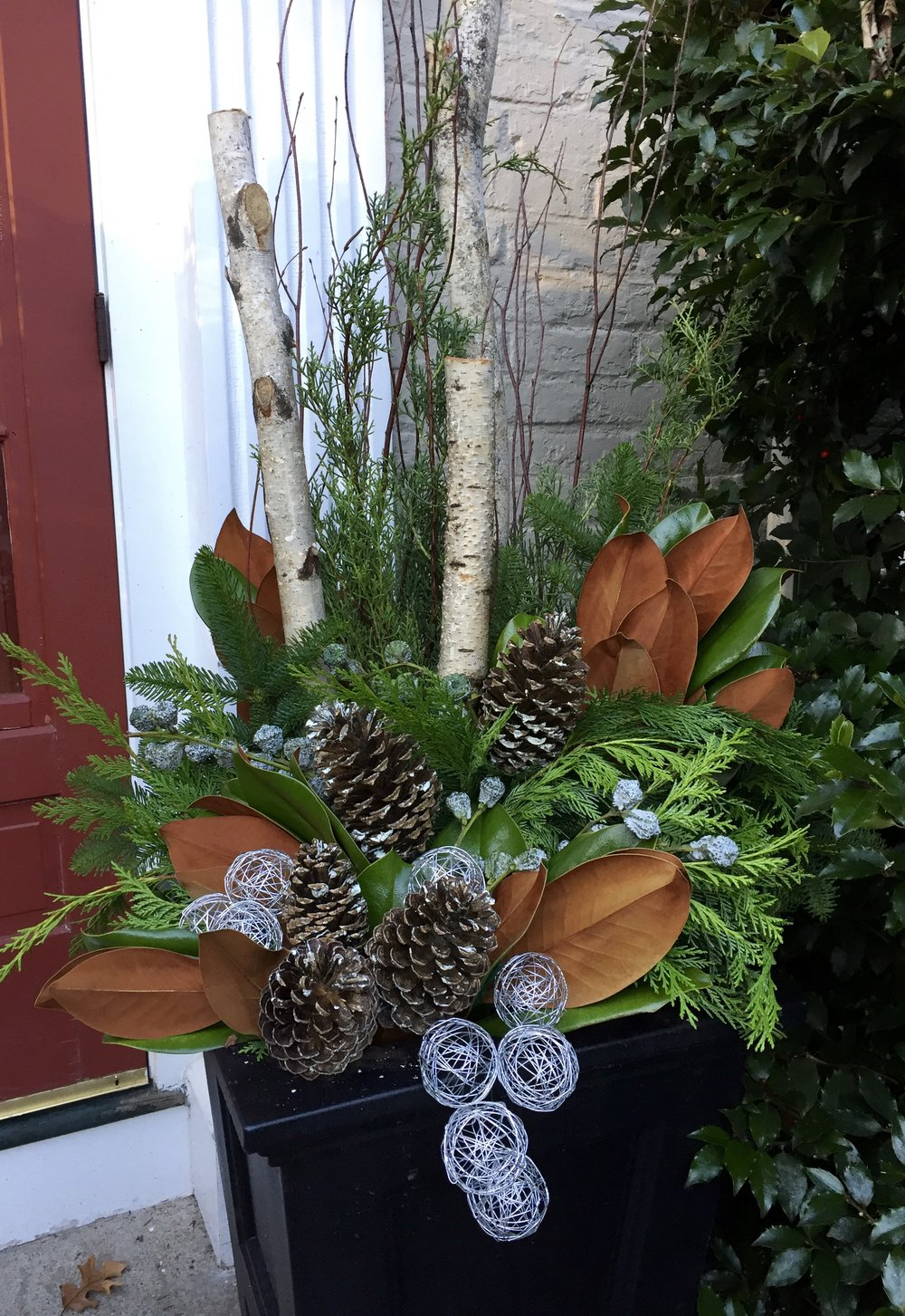 Tall container with greenery, cones and silver accents.