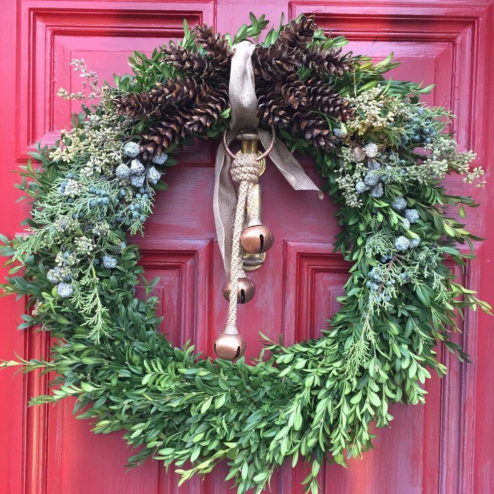 Boxwood wreath with pinecones and mixed greens.