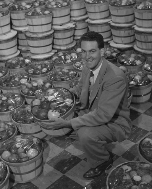 Founder Harold Thomforde shows his holiday fruit baskets containing apples grown in the original Stone Barn Orchard. (circa 1960)