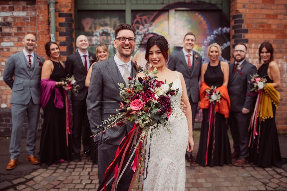 Amy and Ed got married in February at Fazeley Studios in Birmingham's creative quarter. From the elegant grandeur of a renovated 19th century chapel to the versatile blank canvas of the converted factory spaces, there is no more perfect place to host your wedding! They chose a stunning floral colour palete of Ruby reds and hot pinks with a touch of black to match the bridesmaid dresses. The Sleeping Flower Company put together a spectacular array of florals in their chosen colours, including cabbage and peony roses, berries, anemone, eucalyptus, setaria, wheat, oats and a variety of seed pods and other gorgeous fillers. The stunning colours were offset by the wonderful black bridesmaids dresses and the bride's beautiful, cream wedding gown. Simply Spectacular!  PHOTOGRAPY - Gemma Gaskins Photography  https://m.facebook.com/gemmagaskinsphotography/