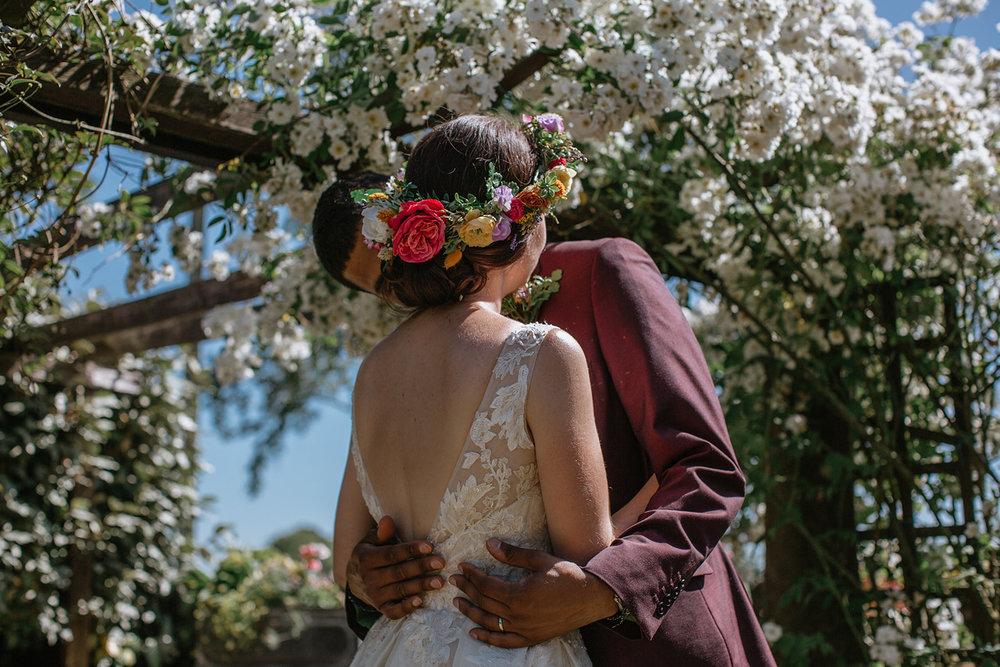 Emma and Ram got married on a beautiful warm and sunny day in June, 2018. They were married at Miltown Baptist Church in Belfast and held their marquee wedding reception in Emma's parent's garden. Emma wanted a mix of  brightly colours flowers to reflect her wedding theme of 'country garden with a tropical twist.' Ram's family Island of Mauritius is home to many brightly coloured flowers and plants and so we chose a beautiful selection of cabbage roses, peonies, anenomes, wild grasses and seed pods  in pinks, yellows, oranges and blues for the bouquets, floral crown and buttonholes. We think that they all looked perfectly stunning!