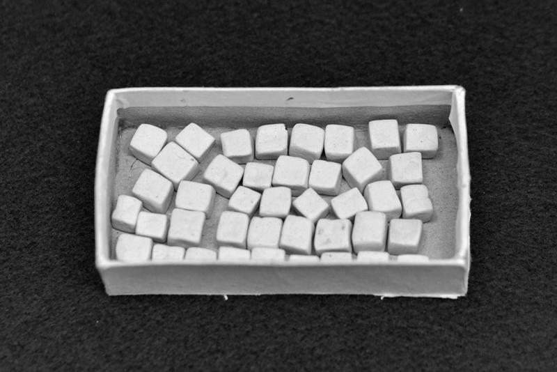 petits carrés en forme de céramique   douze cubes de céramique pouvant générer la création d'une oeuvre, nécessite son activation par un auteur (actuellement par  Marc Buchy ) dimensions variables pièce unique