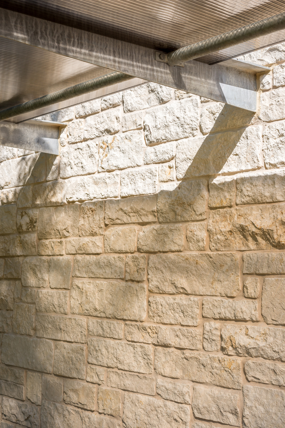 Shadow play with limestone, galvanized outriggers, and the translucent polygal awning.