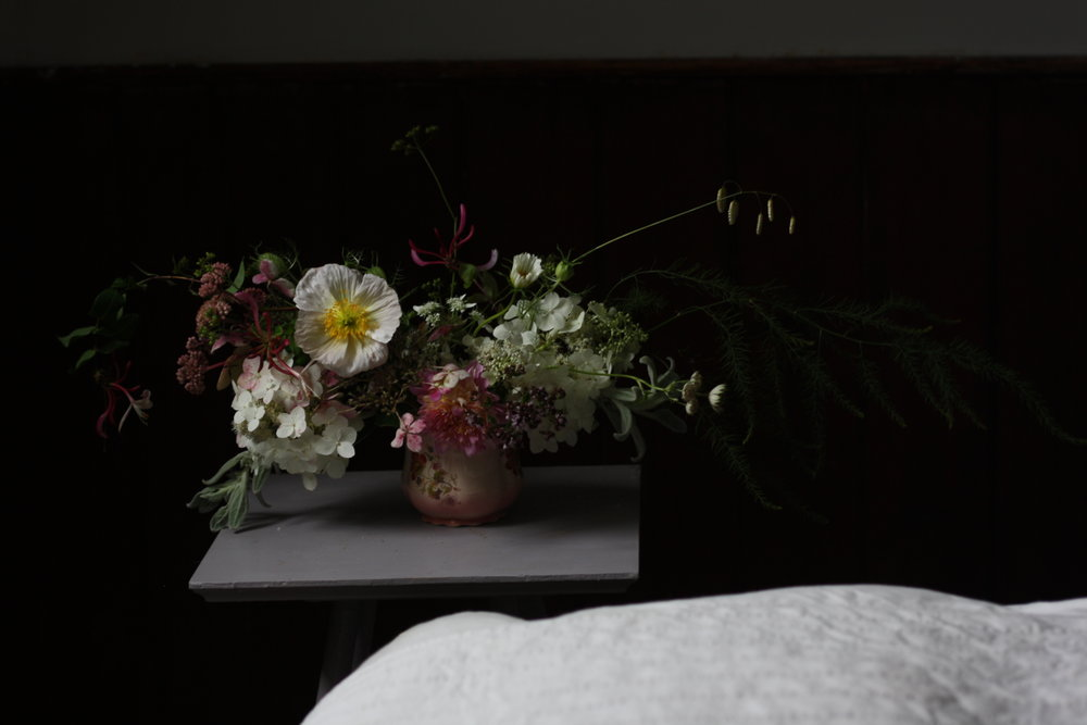 table arrangement with hydragea, honeysuckle, brizia maxima and Colibri iceland poppy 'Bianco'. Hedgerow Flower Company, Nova Scotia, Canada