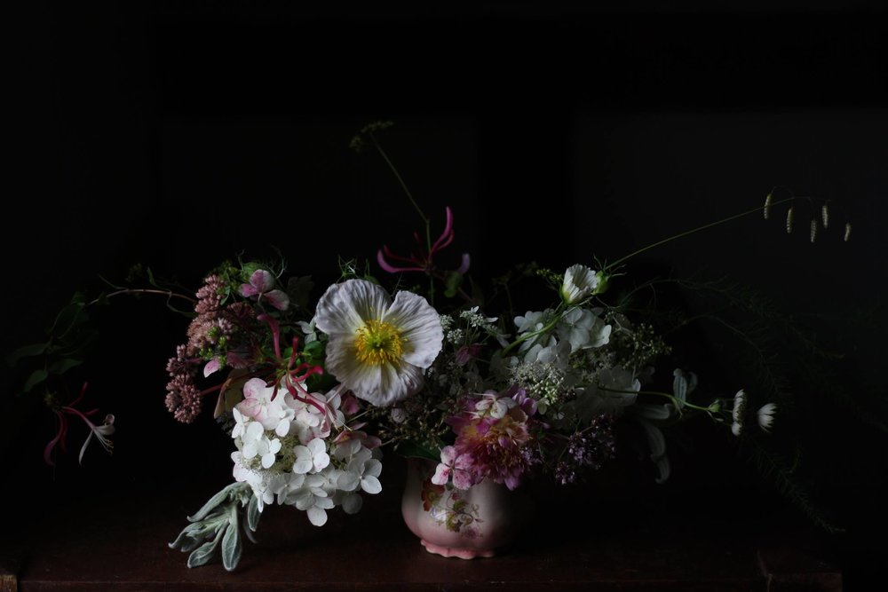 Seasonal wedding centerpiece from Hedgerow Flower Company an organic flower farm and wedding florist in Nova Scotia. Arrangement includes iceland poppy, hydrangea, dahlia, astrantia, honeysuckle, sedum, quacking grass, asparagus, lambs ear and marjoram.