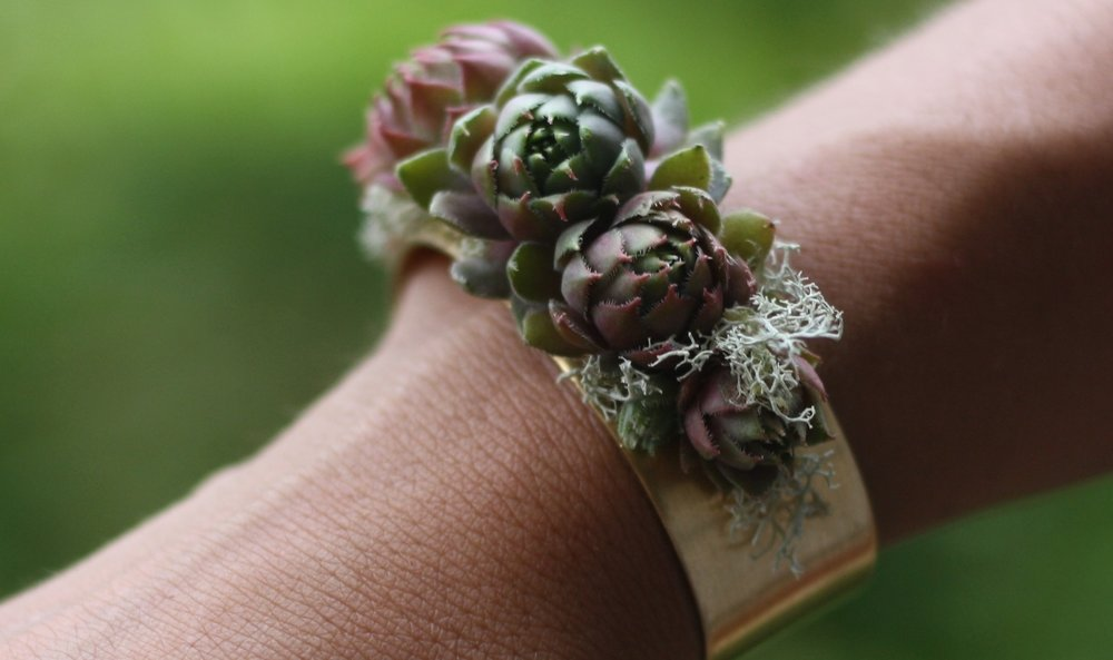 Wedding corsage alternative: Beautiful brass cuff featuring succulents and lichen. Florist: Hedgerow Flower Company. Venue: Digby Pines, NS.