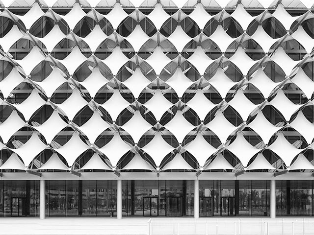 The King Fahd National Library is one of the most significant cultural centers in Saudi Arabia. Located in the capital Riyadh, the structure is a hybrid of new technology and traditional styling. The facade is defined by the three-dimensional steel wire textile filigree façade used as sun and heat protection.  The façade controls daylight to create soft internal lighting, reflecting direct sunlight while still allowing plenty of daylight to enter the building. The design is high performing, effective, and contemporary, and what's better is that it does all this with design strategies that are centuries old, executed with innovative technology.  Source: gerberarchitekten.de  #TensileMembrane #TensileMembraneArchitecture #TensileArchitecture #Architecture #Engineering #Energy #Facade #Design #Riyadh #SaudiArabia #History #KingFahdNationalLibrary #GreenBuilding #Performance #Culture #Arab