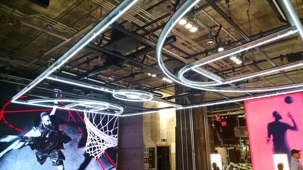 Directional speakers and subwoofers focus audio to a zone beneath the illuminated basketball court.