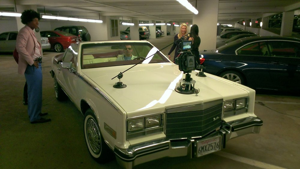 strapping the scarlet on the bonnet of a 1980s-vintage cadillac eldorado.