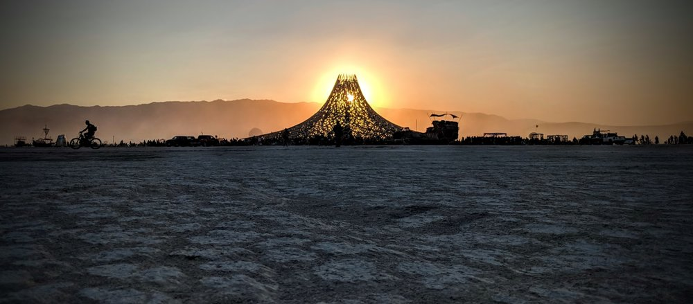 the sun sets behind the 2018 temple.