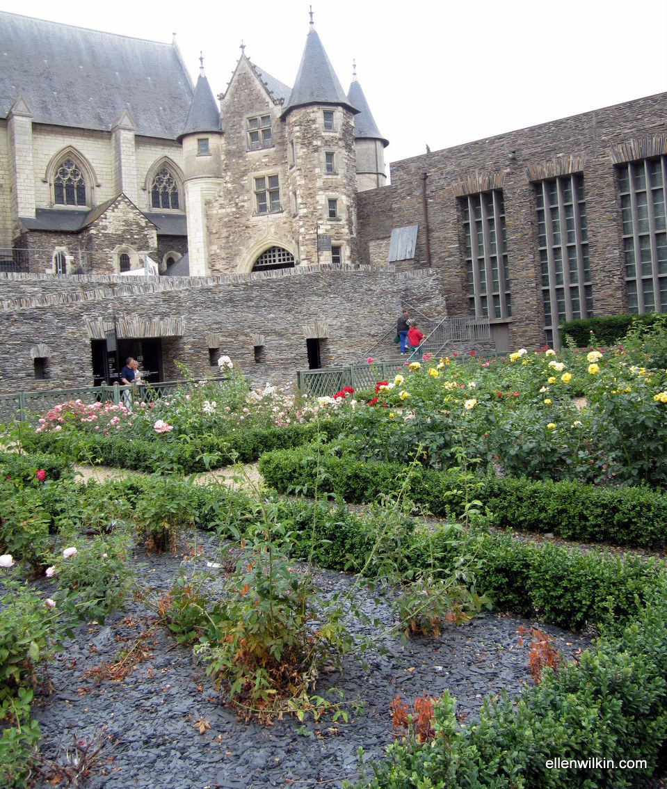 The entrance to the museum gift shop and to the remains of the Roman baths seen from the formal gardens that grace the courtyard in front of the 12th century castle wall. The southeast end of the Apocalypse Tapestry hall is at the top right.