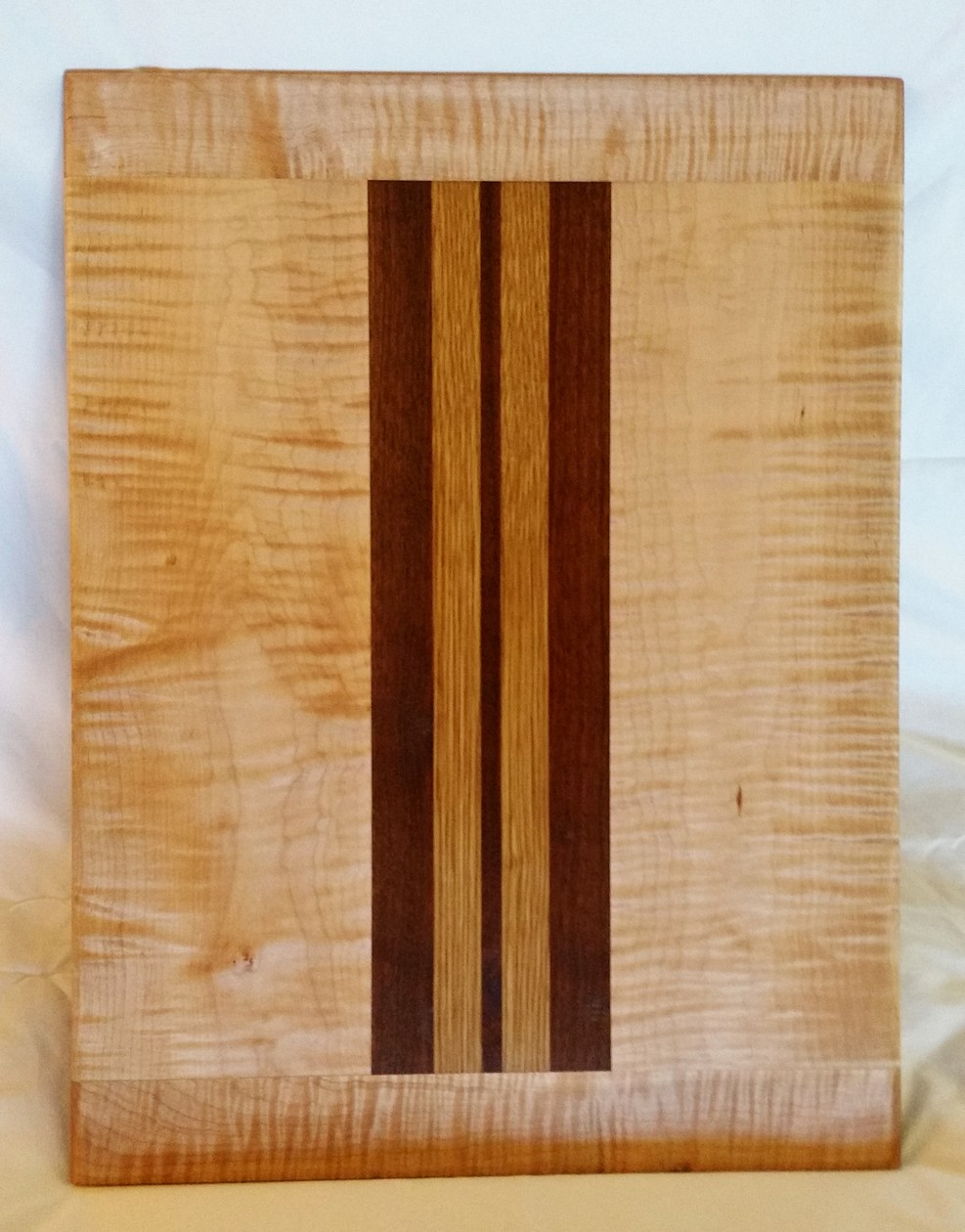 Stunning curly maple is paired with black walnut and white oak to create this captivating serving board