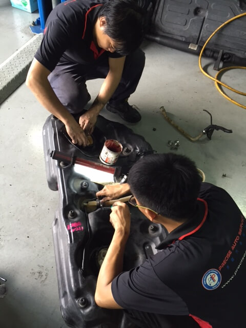 Our diligent mechanics working on the fuel tank.