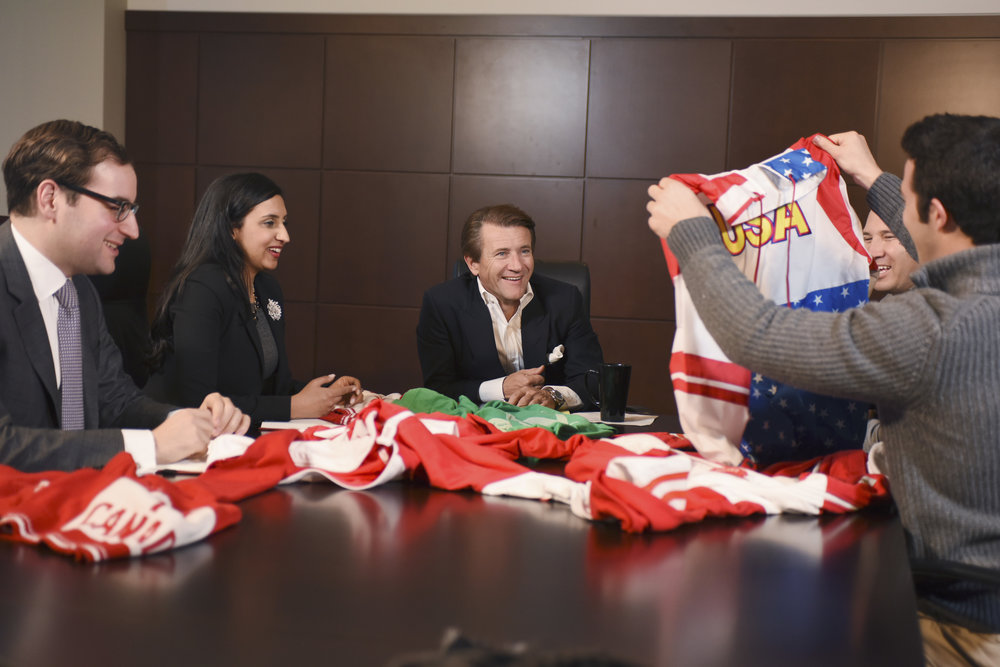 """Nick Morton and Evan Mendelsohn, cofounders of the """"ugly sweater"""" apparel company Tipsy Elves, show their wares to Shark Tank star investor Robert Herjavec. (Courtesy ABC Press)"""