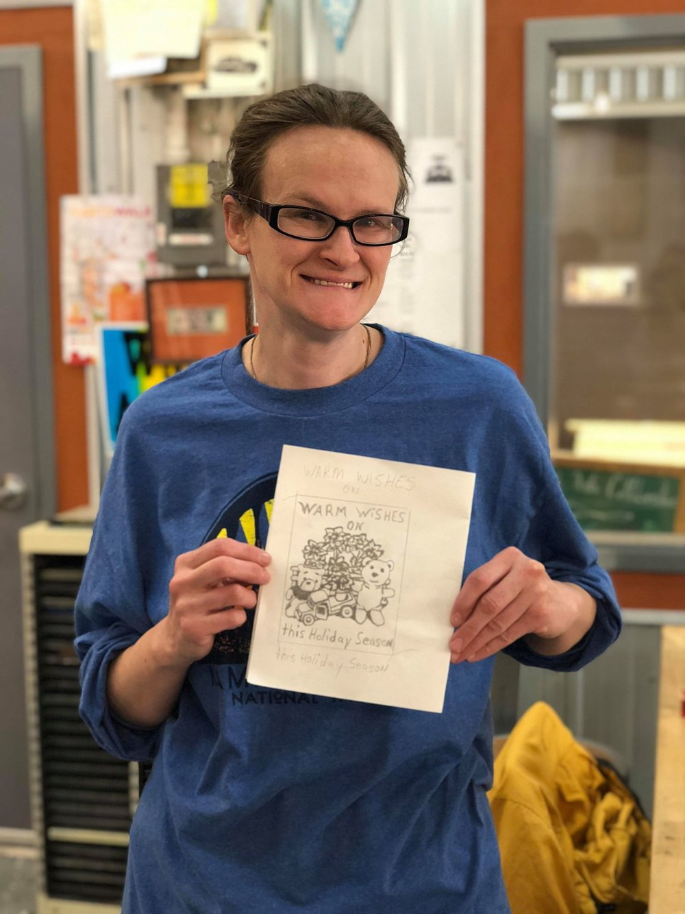 Mary holding a sketch of her linoleum carving.
