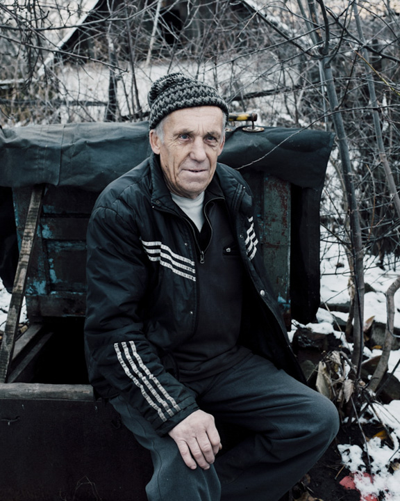 Vasily sits on the hatch of his basement which he has been using as a bunker since the conflict began. He keeps it well-stocked with food for him and his son to survive a minimum of ten days in the self-made bunker. At any moment they can leave everything behind and take shelter in the basement until the shelling is over.