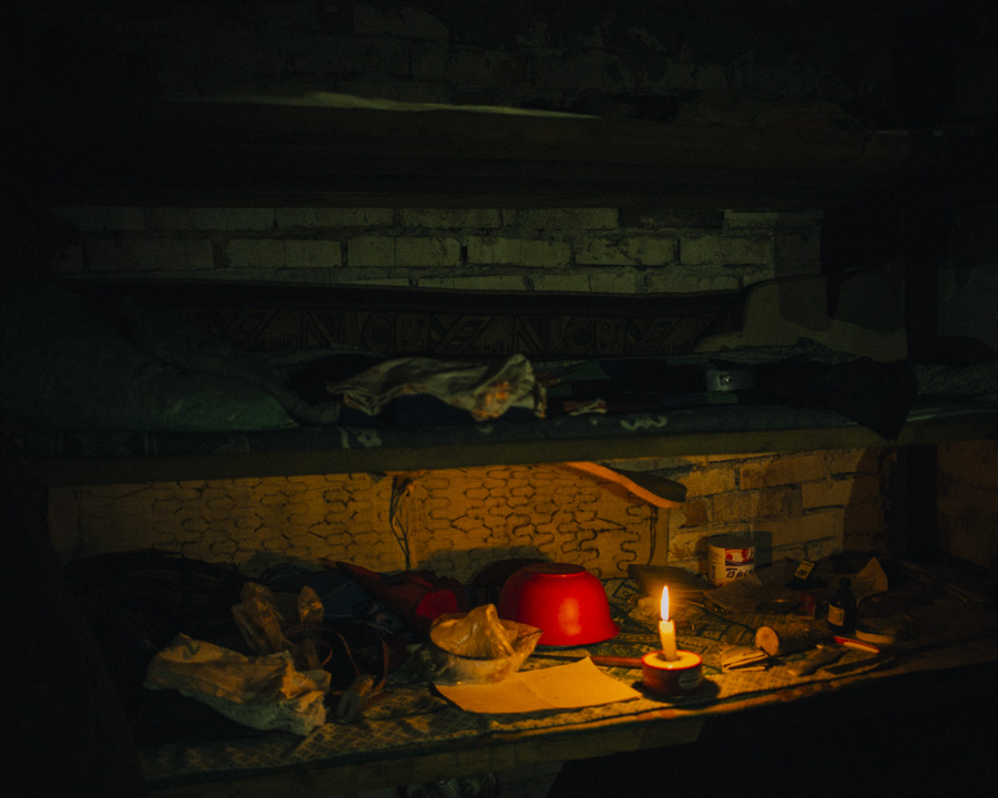 In the basement of a destroyed house complex is an self made bunker room where people are living since more then one year. The bed is an old shelf on the wall.  No electricity, no water, no gas.