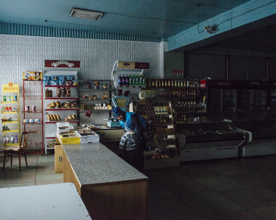 Yuliya, a UNHCR volunteer, was talking with the boy in this shop around horlivka.  There was no electricity and no heating. The temperature was freezing inside but it was still open.