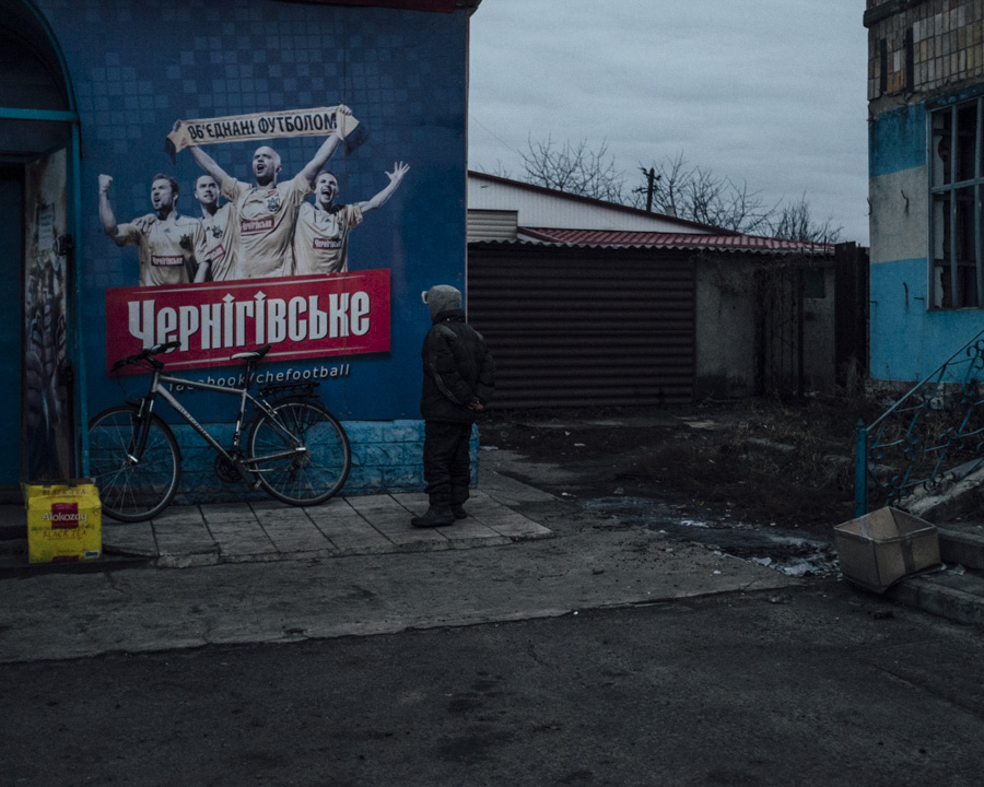 At the checkpoint in Karlivka, where the highway leads straight to Donetsk, there is the last working store for groceries.  The small boy was staring at this Soccer advertisement for a couple of minutes.