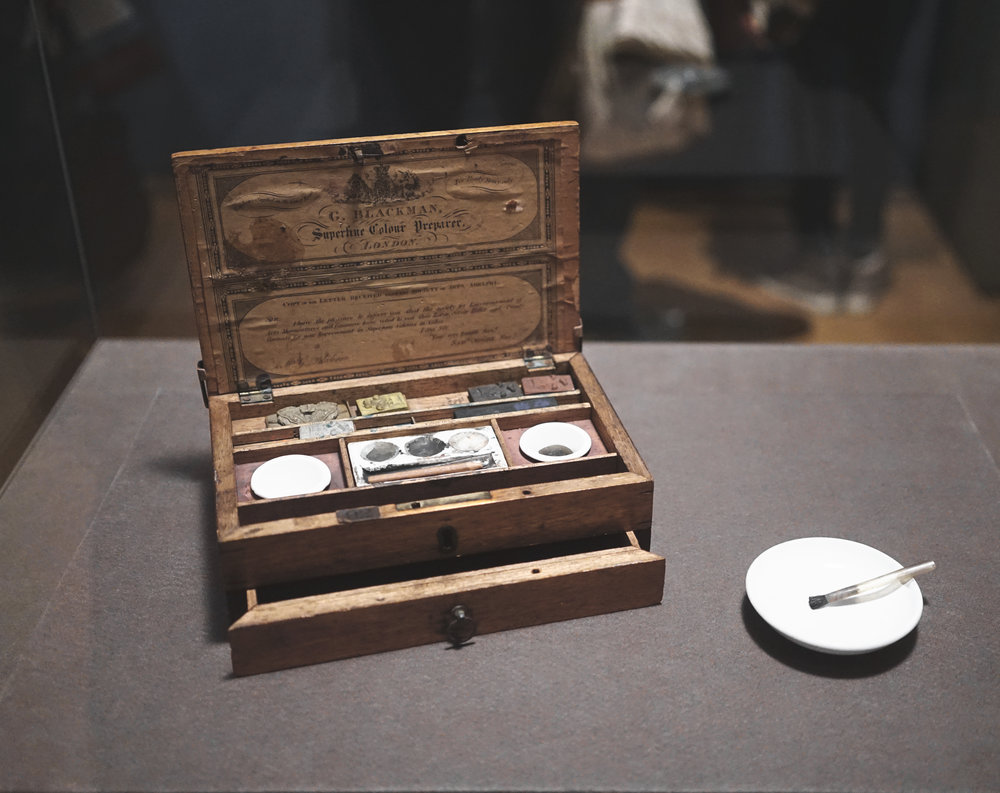 "Brontë's Paintbox  Brontë filled her portable oak paintbox with the essential tools of a middle-class-amateur artist. It contains twenty-three cakes of soluble watercolor in a variety of hues. To produce paint, Brontë would dip the cake in wake and rub it onto one of the porcelain saucers. One of her hog's-hair brushes is fitted to a quill. The symbol on the unused cakes- three ostrich feathers rising through a coronet- is the heraldic badge of the Prince of Wales and the trademark of the supplier, or colorman, George Blackman. His trade card, which advertises his services as a ""Superfine Colour Preparer,"" is adhered to the inside of the lid along with a copy of testimonial from the Society for the Encouragement of Arts, Manufactures and Commerce (known today as the RSA)."