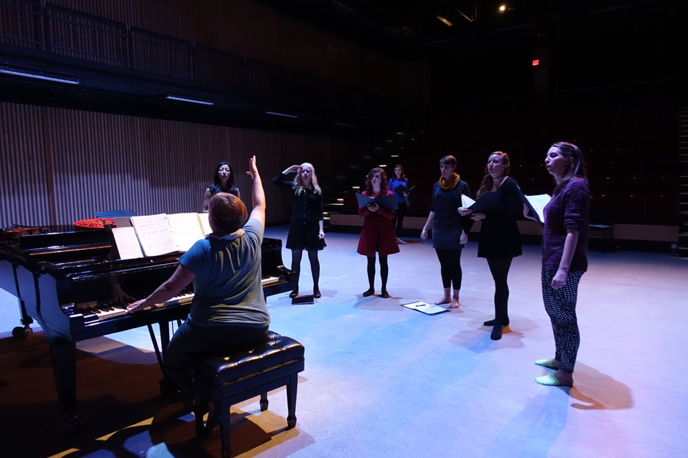 Musical Director Caitlyn Hayes rehearses with the youth chorus for the In-Concert Presentation of Les Filles Du Roi. Pictured are chorus members Patrice Bowler, Karliana Dewolff, Marie Jose Herrera, Sidney Klips, Geneva Perkins, and Lindsay Warnock