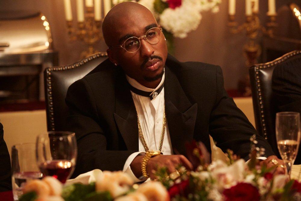 A screenshot of Demetrius Shipp Jr. portraying Tupac in a dinner scene.