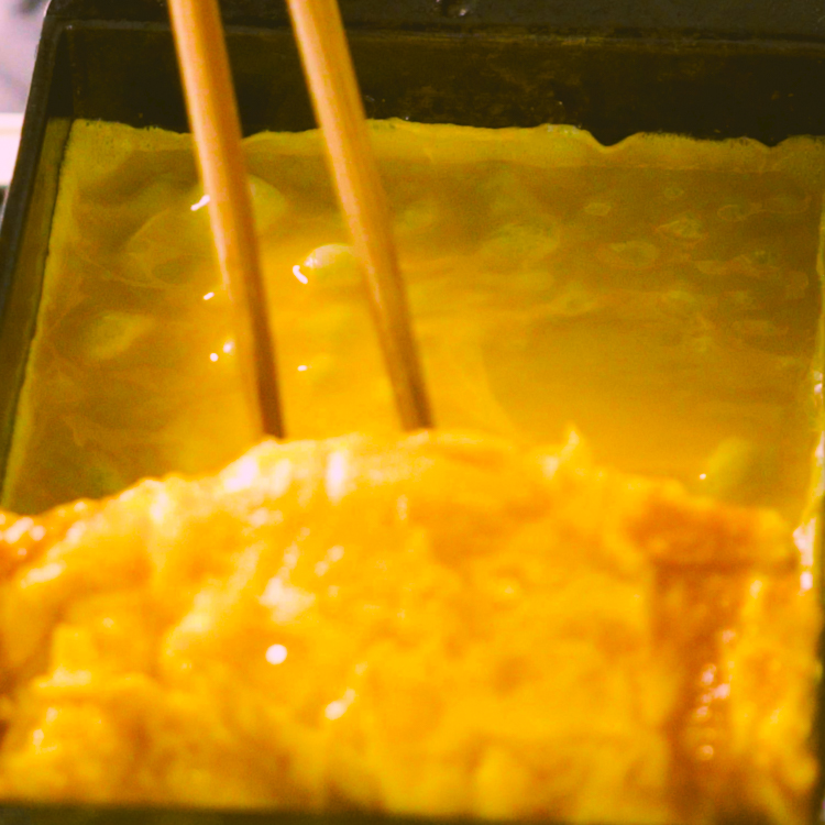 4.  菜箸で、3を奥によせて、空いたところに残りの卵液の1/3を流す。卵焼きを少し持ち上げて、下にも卵液が回るようにする。