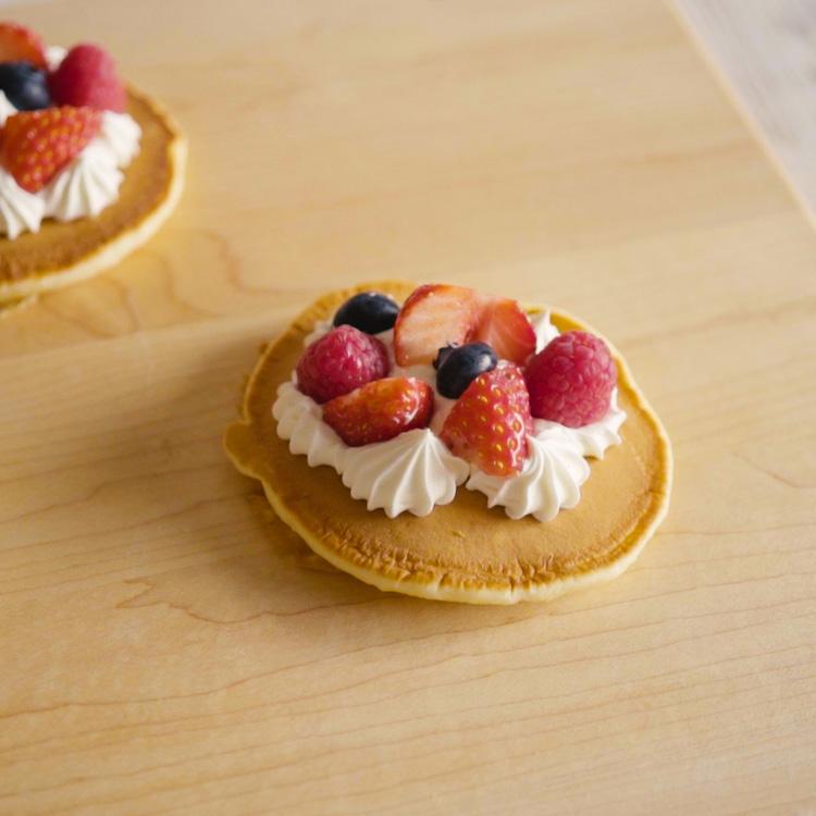 6. パンケーキの間に切ったいちごをはさみ絞り袋に入れたクリームを絞ります。