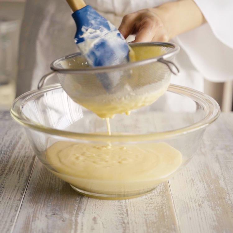 6. 5に薄力粉をふるい入れなめらかになるまで混ぜ、ボウルにこし入れます。  ※こすことでなめらかで口当たりのよい生地になります。