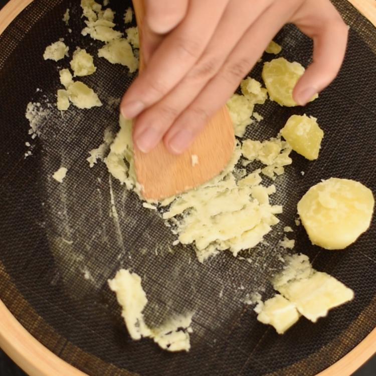 4. 茹で上がった芋をざるにあげ、キッチンペーパーなどで水気をよく切り、熱いうちに木べらを使って少量ずつ裏ごす。こし終わったら、裏面の目に残った芋を丁寧に木べらで集めて、まとめる。  ※裏ごし器がない場合は、目の細かいざる(ステンレス製)でも構いません。越す回数は、目の細かさで調節します。