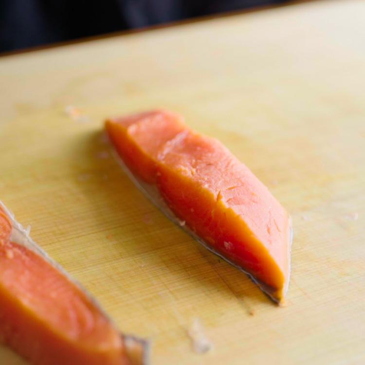 3. 鮭に酒をふりかけて5分程度置き、ペーパーで水気を拭く。骨を切り落とし、巻きやすい大きさに切る。  ※酒をふることで臭みが抜け、仕上がりがふっくらになる。