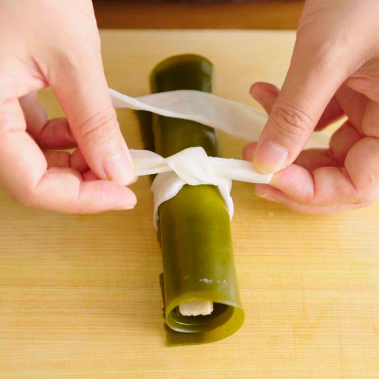 4. 昆布を敷いて上に鮭を置き、巻いていく。かんぴょうできつめに結ぶ。