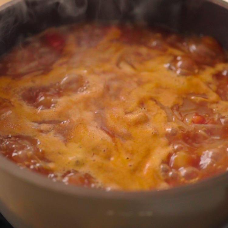 5. 赤ワイン、カットトマト缶、トマトペースト、ハチミツ、水を加えて約1時間半煮る。