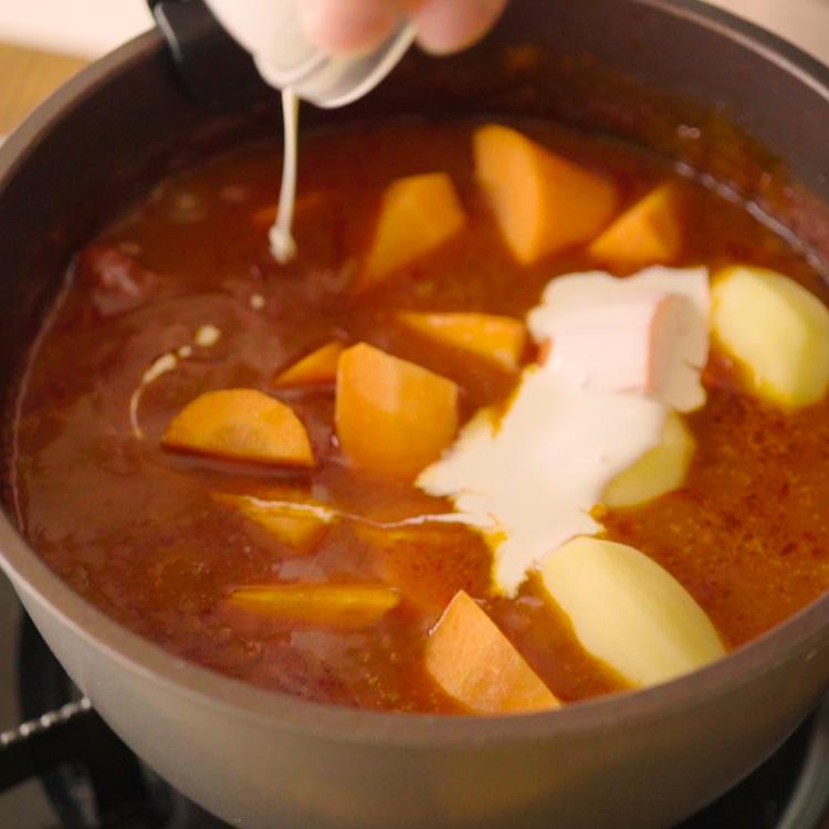 6. 途中で生クリーム、ニンジン、ジャガイモを加えて煮る。