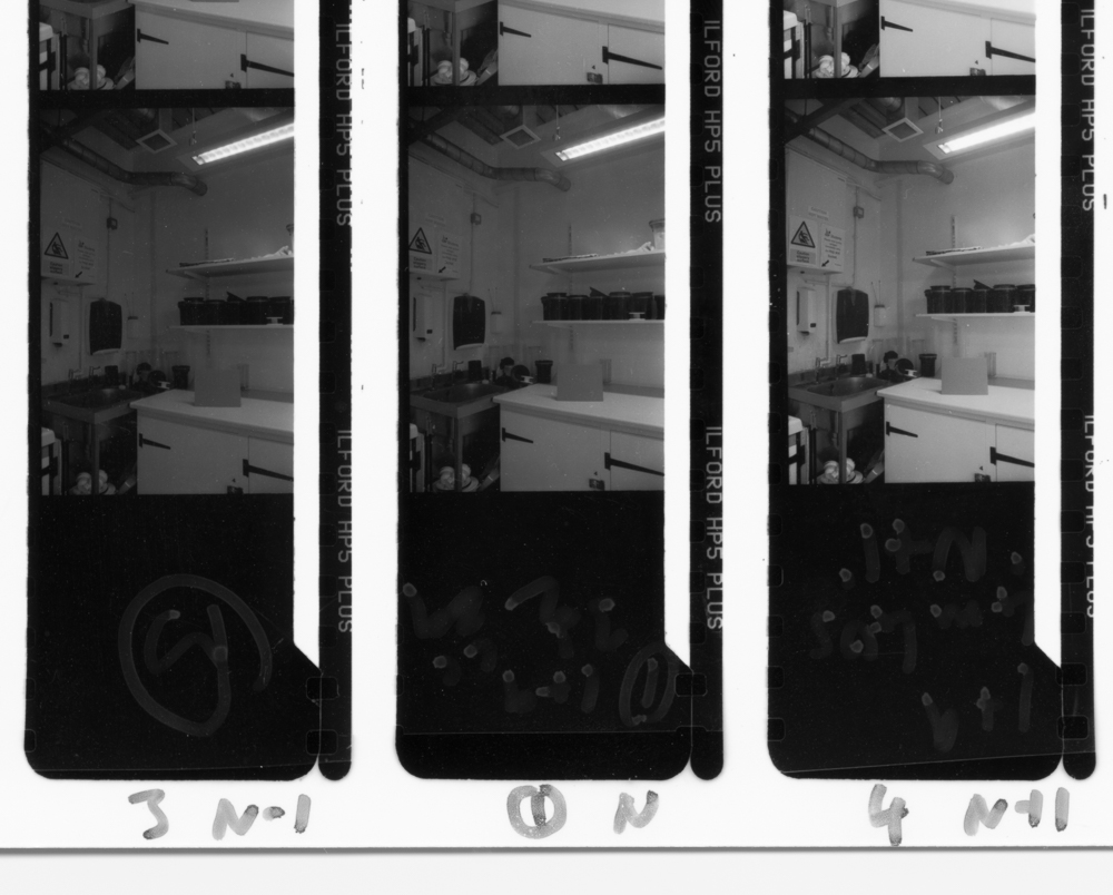 Contact print showing 'normal' development (centre), under-development (left) and over-development (right)