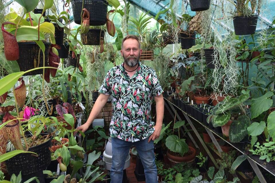 Mike Clifford in his tropical greenhouse, surrounded by just some of his incredible plant collection.