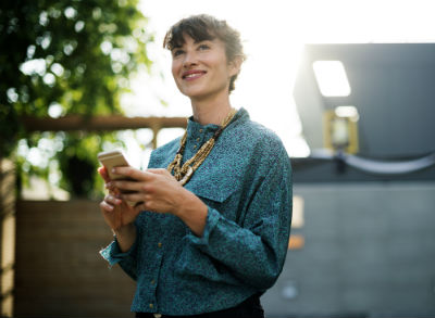 Woman looking up and smiling while on her phone