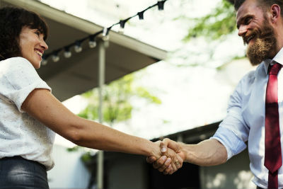 Business man and woman shaking hands whilst smiling