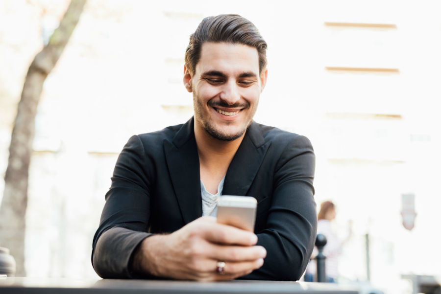 Man smiling whilst looking down on mobile