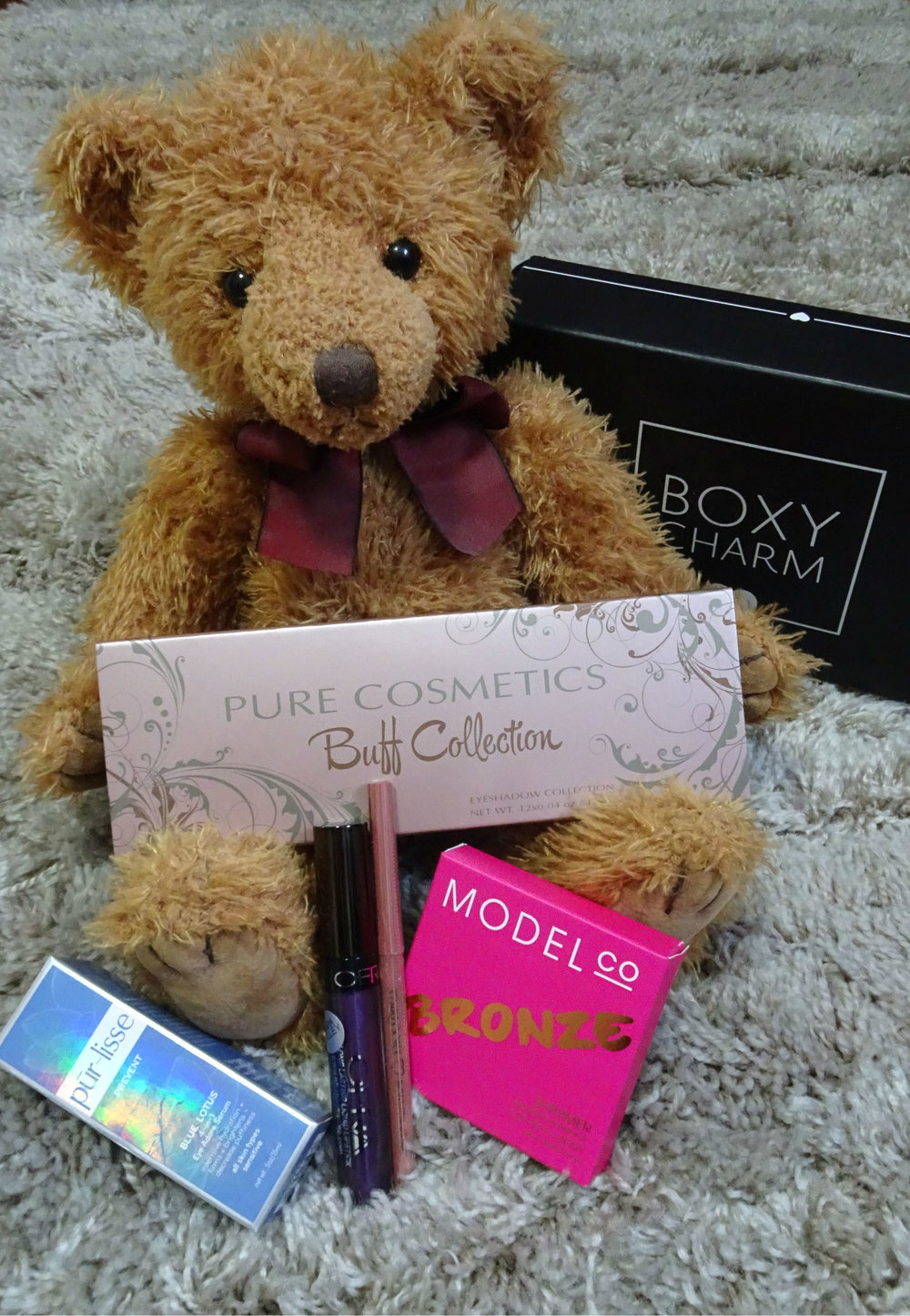 Teddy showing off my December Boxycharm contents