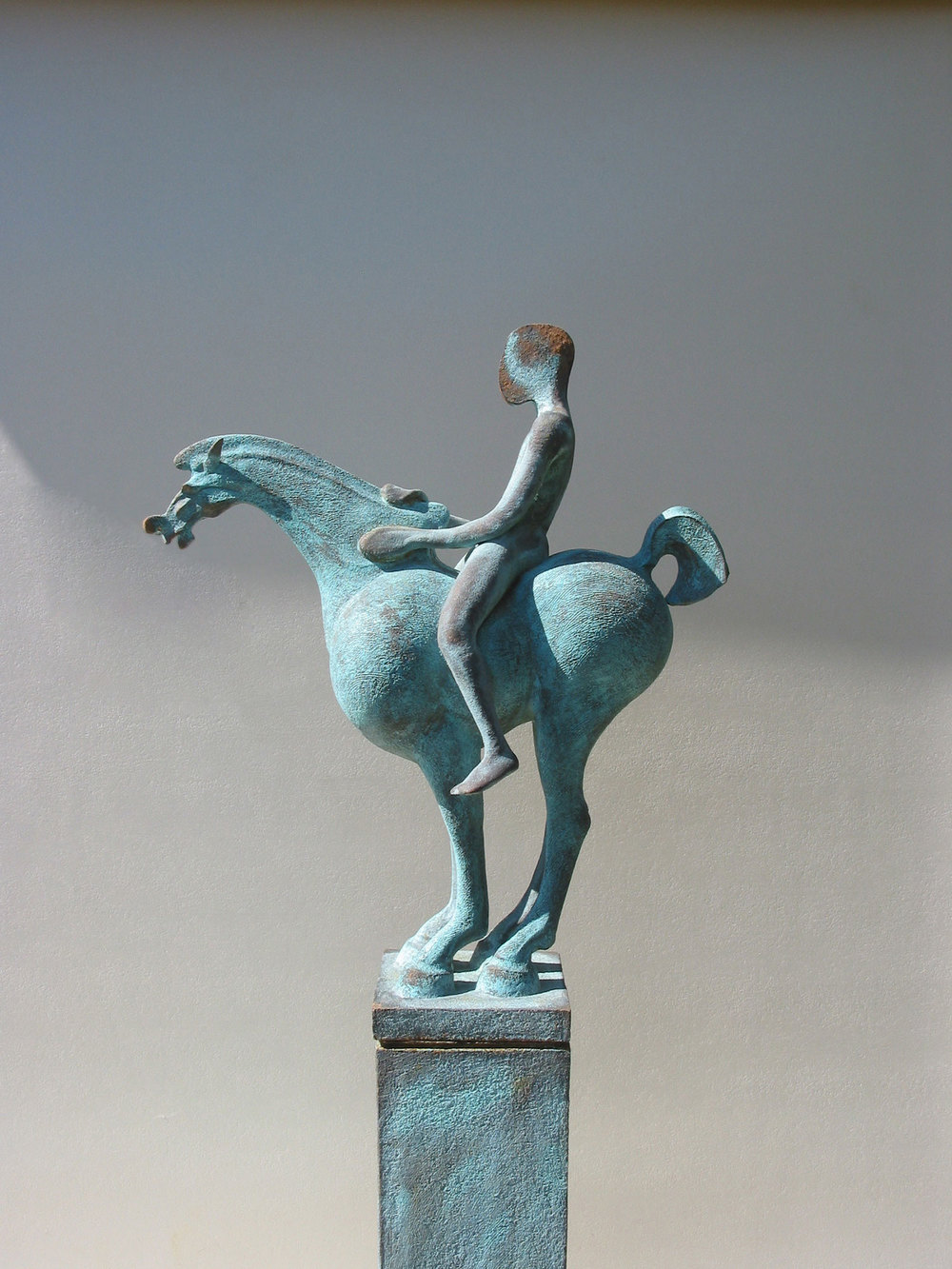 Chloros   ©  126 cm high x 50 cm wide  Unique  Chlorus - Greek lexicon for pale green. The piece takes its energy from a Chinese dynamic, though paradoxically it is hauntingly still.  The horse's head is diminutive - a classical technique which enhances presence in the body.  Though it is not apparent from this angle, viewed face-on, in both Tang Blue and this sculpture, the figure's head is pared down to a mere slice, sitting on the shoulders like a penny - perhaps a gradual path to abstraction.