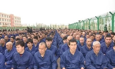 "Photo reported to show detainee in a Xinjiang Re-education Camp located in Lop County listening to ""de-radicalization"" talks.  Photo Source: Wikipedia Xinjiang Re-education Camp Lop County"