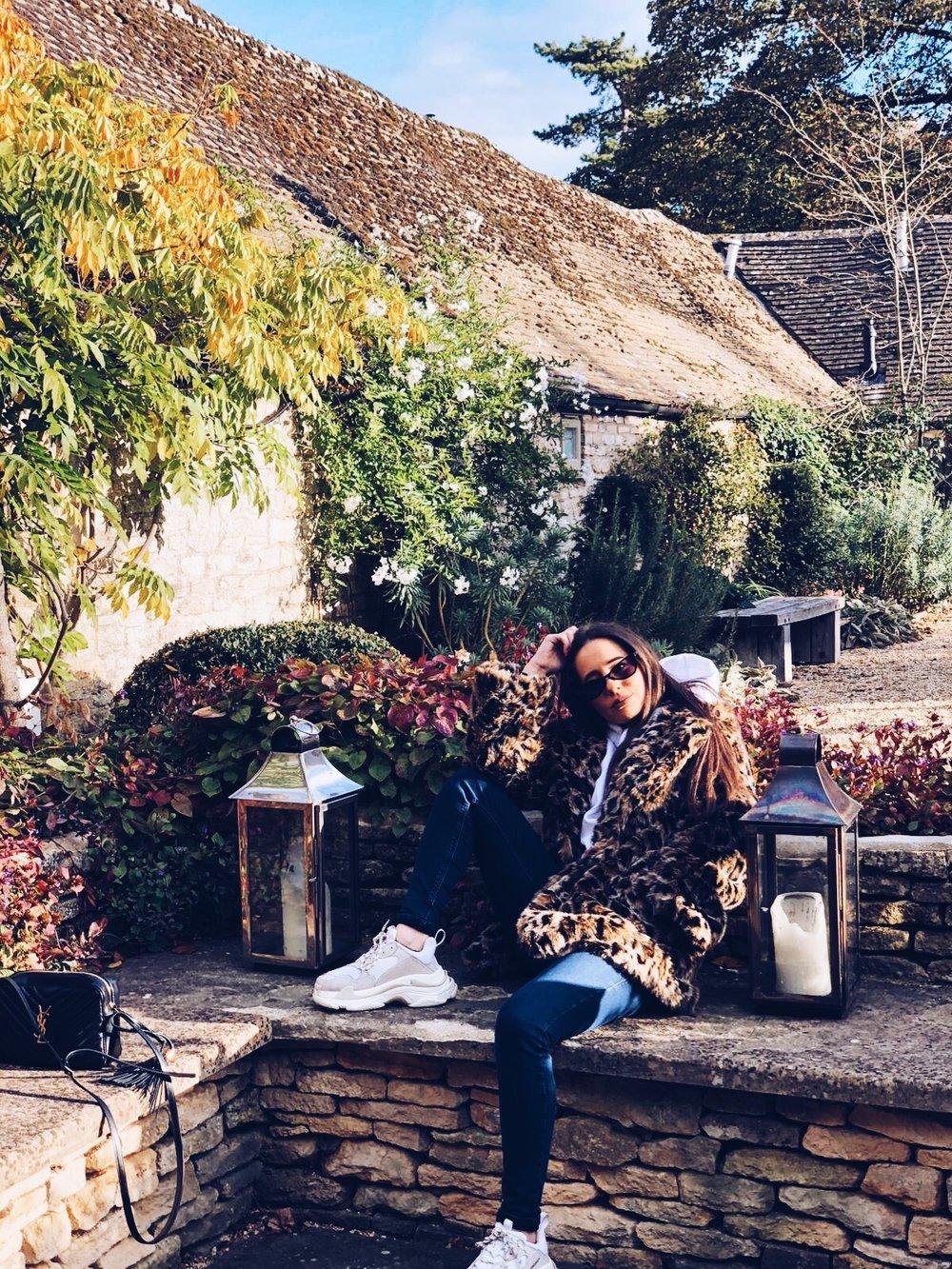 A Wears   Leopard Coat - H&M    Bag - YSL    Sunglasses - Balenciaga    Trainers - Balenciaga    Jeans - J Brand