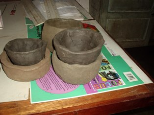 These pots are made from clay soil, collected from a nearby anthill. We wet the soil and modelled it into assorted items - pots, flower pots, dolls, cars and animals.