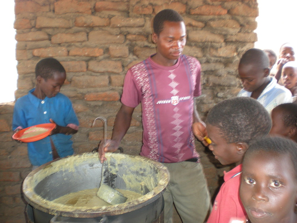 The photograph shows the chairman of the PTA at Napache School serving the porridge.