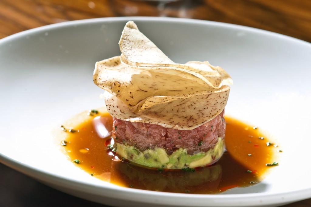 Picture of STK Tuna Tartare layered with avocado at base, tuna in the middle and chips on top.