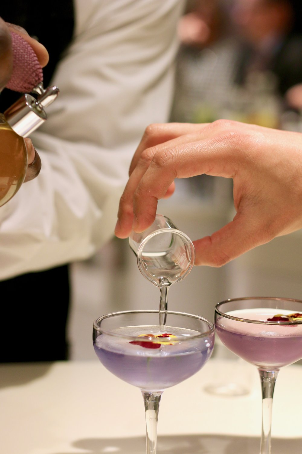 The floral cocktail changes colors as it is prepared.